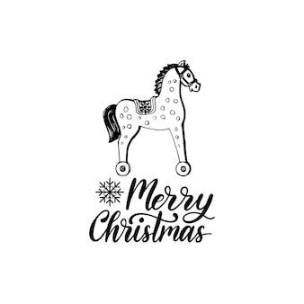 Frohe weihnachten schriftzug auf weißem hintergrund. hand gezeichnete spielzeug holzpferd illustration. frohe feiertage grußkarte, plakatschablone.