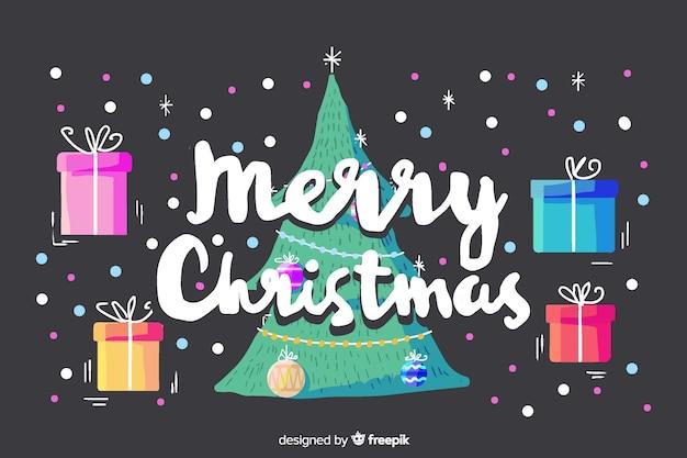 Frohe weihnachten-schriftzug mit geschenken und weihnachtsbaum