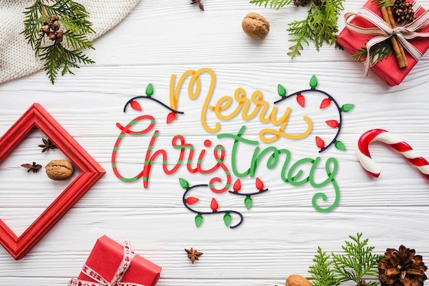 Frohe weihnachten-schriftzug mit rahmen und geschenken