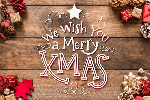 Frohe weihnachten-schriftzug mit tannenzapfen und geschenken
