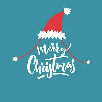 Frohe weihnachten-titel in roter weihnachtsmütze auf blauem hintergrund. lustiges kartendesign.