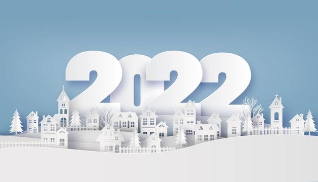 Frohe weihnachten und ein glückliches neues jahr 2022, countryside village in winterpapiercollage und scherenschnittstil mit digitalem handwerk.