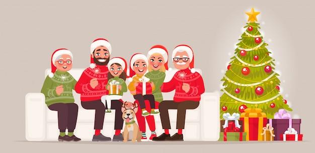 Frohe weihnachten und ein glückliches neues jahr. große familie, die auf dem sofa nahe bei dem weihnachtsbaum mit geschenken sitzt