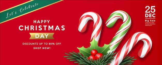 Frohe weihnachten verkauf bunte zuckerstange und stechpalme, kiefernblätter auf rotem hintergrundgrußkarte