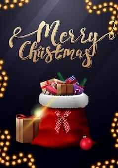 Frohe weihnachten, vertikale blaue postkarte mit goldbeschriftung und santa claus-tasche mit geschenken