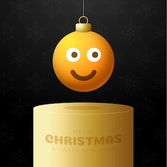 Frohe weihnachtskarte mit lächeln emoji-gesicht auf sockel. vektorillustration im flachen stil mit weihnachtsbeschriftung und -gefühl in der weihnachtskugel hängen am faden auf hintergrund