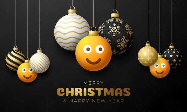 Frohe weihnachtskarte mit lächeln emoji-gesicht. vektorillustration im flachen stil mit weihnachtsbeschriftung und -gefühl in der weihnachtskugel hängen am faden auf hintergrund