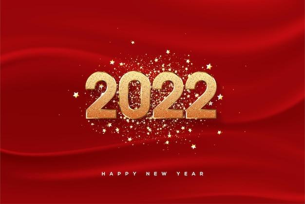 Frohes neues jahr 2022 mit goldenen zahlen und glitzer auf rotem stoffhintergrund