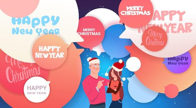 Frohes neues jahr banner mit mann und frau in santa hats über abstrakten chat blasen frohe weihnachten