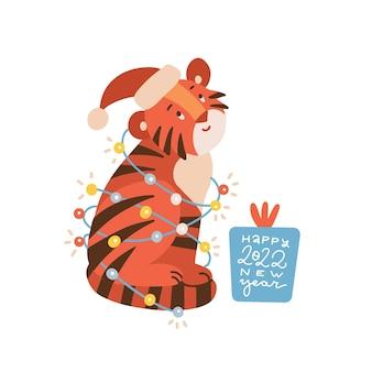 Frohes neues jahr grußkarte kleines tigerjunges mit einer geschenkbox mit einer aufschrift, die in einem k...