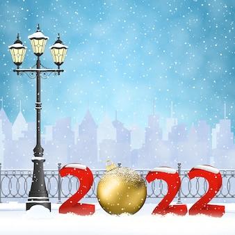 Frohes neues jahr und frohe weihnachten winterstadtbild mit leuchtender straßenlaterne, schneeflocken. konzept für gruß- und postkarte, einladung, vorlage, 2022 mit weihnachtskugel