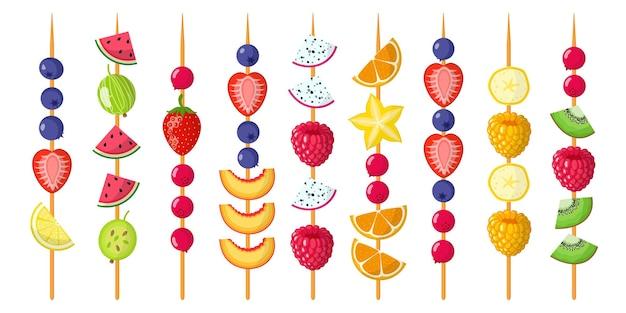 Fruchtkanapees mischen sich auf holzspießen. erdbeeren, blaubeeren, himbeeren, wassermelone, kiwi, banane, mandarine.