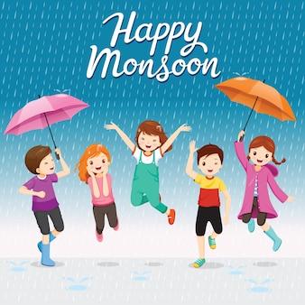 Fünf kinder mit regenschirm und regenmantel springen spielerisch in den regen, glücklicher monsun