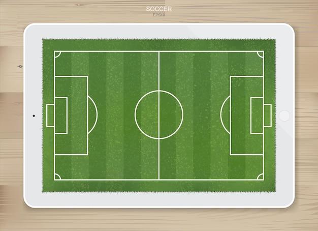 Fußball-fußballplatz-hintergrund in der anzeige des tablet-bildschirms zum erstellen einer fußballspiel- und fußballtaktikidee. vektor-illustration.