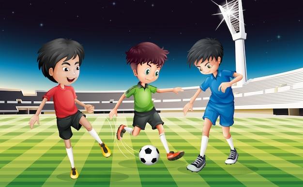 Fußballspieler, die ball auf dem gebiet nachts spielen