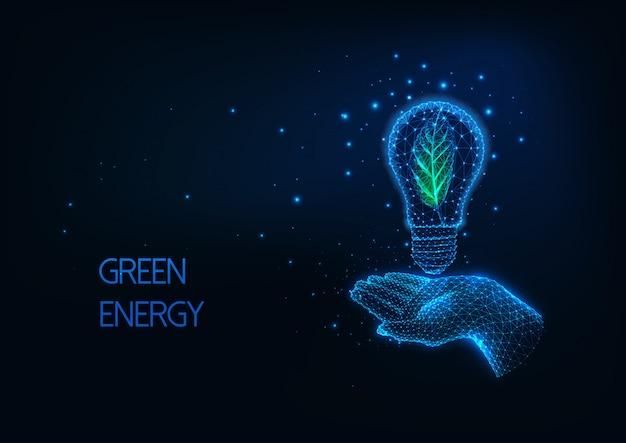 Futuristisches grünes, erneuerbares energiekonzept mit glühender niedriger polygonaler hand, die glühbirne hält