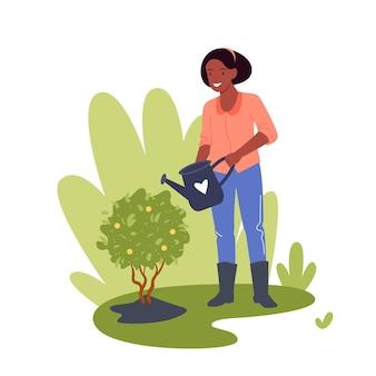 Gärtnerarbeiterin arbeitet im garten und gießt zitronenbaum mit dose