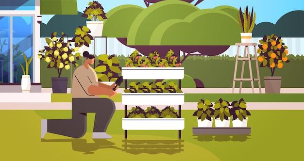 Gärtnerin mit schaufel kümmert sich um topfpflanzen im hinterhofgewächshaus oder hausgarten horizontal