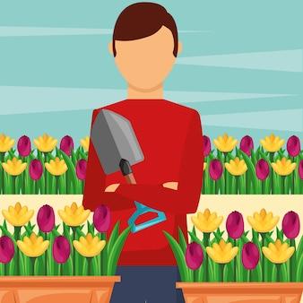 Gärtnermann, der schaufel mit den eingemachten blumengartenarbeit hält