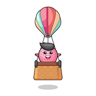 Garnball-maskottchen, das einen heißluftballon reitet, süßes design
