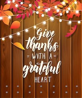 Geben sie dank mit einem dankbaren herzen - erntedankfest, das kalligraphiephrase auf festlichem hölzernem hintergrund mit herbstlaub und girlande beschriftet