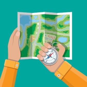 Gefalteter papierstadtplan und kompass in händen