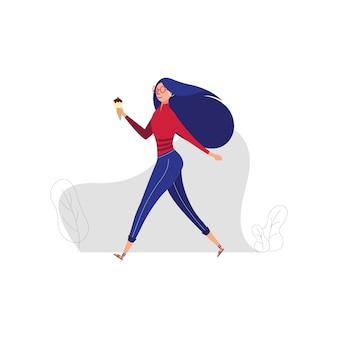Gehende dame mit eiscreme, junges weibliches modell, das eistüte draußen isst. sommerkonzept