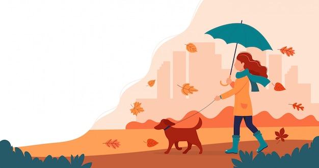 Gehende frau ein hund im herbst mit regenschirm.