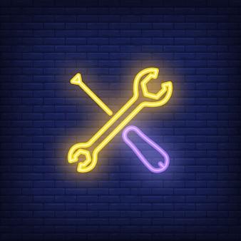 Gekreuzter schraubendreher und schlüssel auf ziegelsteinhintergrund. neon-artillustration.