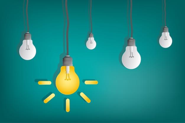Gelb - weiße glühlampe und draht im papierkunstkonzept auf isolatgrünhintergrund