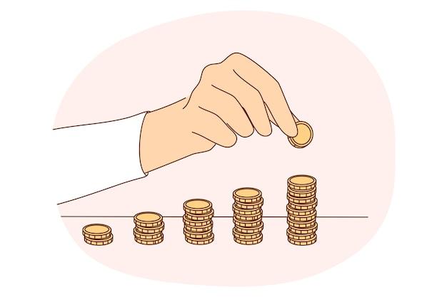 Geldersparnis, münzen, budgetkonzept. hände der person, die stapel der goldenen münzen auf dem tisch macht