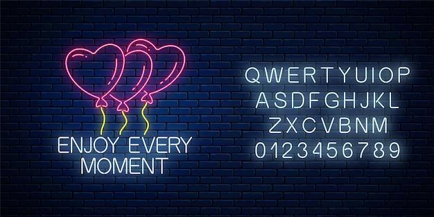 Genießen sie jeden moment - leuchtende neon-inschriftenphrase mit herzförmigen luftballons auf dunkler backsteinmauer mit alphabet.