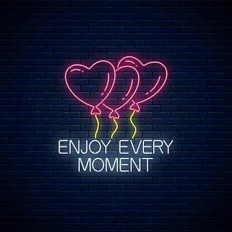 Genießen sie jeden moment - leuchtende neon-inschriftenphrase mit herzförmigen luftballons. motivationszitat.