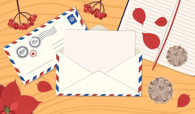 Geöffneter umschlag mit brief auf dem tisch. ein tisch mit briefumschlag mit brief, notizbuch, viburnum, zapfen, weihnachtsstern. ein konzept des briefversands, eine grußkarte für freunde ..
