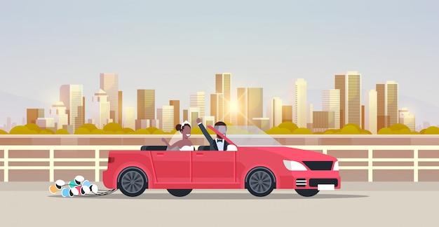 Gerade verheiratet bräutigam braut auf road trip fahren cabrio auto paar in liebe hochzeitstag konzept stadtbild hintergrund horizontale wohnung
