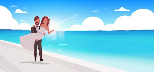Gerade verheiratet bräutigam hält braut auf händen romantisches paar stehend meer strand hochzeitstag sommerferien konzept meer hintergrund voller länge horizontal