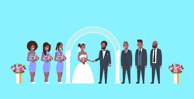 Gerade verheiratete braut und bräutigam mit brautjungfern-trauzeugen, die zusammen nahe bogenhochzeitskonzept blauer hintergrund in voller länge horizontale wohnung stehen