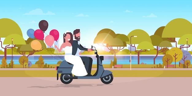 Gerade verheiratetes paar reitet motorroller mit bunten luftballons braut und bräutigam, die spaßhochzeitstag konzeptstadtstadtparklandschaftshintergrund in voller länge horizontal haben