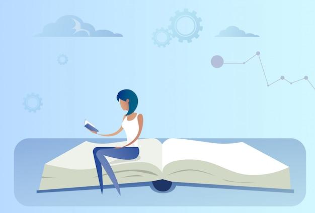 Geschäftsfrau, die am offenen buch liest bildungs-konzept sitzt