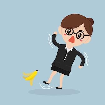 Geschäftsfrau, die auf eine bananenschale rutscht