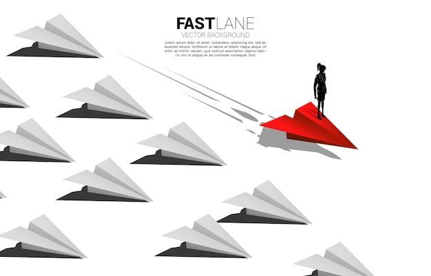 Geschäftsfrau, die auf rotem origami-papierflugzeug steht