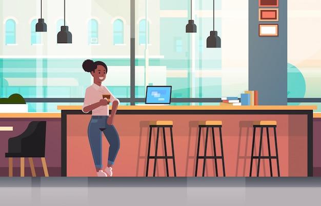 Geschäftsfrau, die auf stuhl am bartheke mit laptop-kaffeepausenkonzeptgeschäftsfrau sitzt, die cappuccino modernes caféinnenraum in voller länge horizontal trinkt
