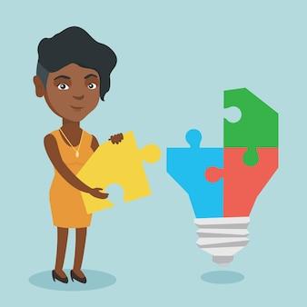 Geschäftsfrau, die die glühlampe hergestellt vom puzzlespiel abschließt