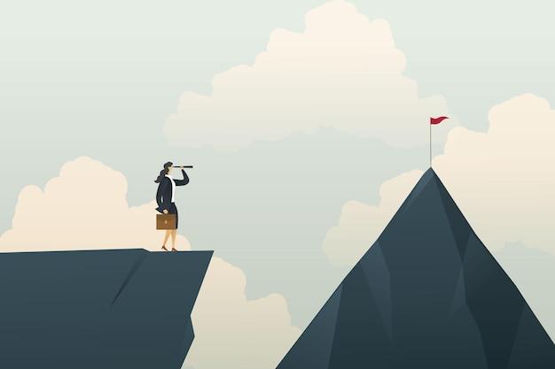 Geschäftsfrau, die durch ein fernglas nach dem weg zum ziel am berg sucht