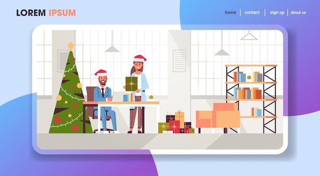 Geschäftsfrau, die geschenkgeschenkbox zum geschäftsmann gibt, der mit frohen weihnachten frohes neues jahr winterferienfeierkonzept moderne büroeinrichtung gratuliert