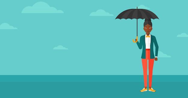 Geschäftsfrau, die mit regenschirm steht.