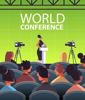 Geschäftsfrau, die rede an der tribüne mit mikrofon auf vertikaler illustration des internationalen weltkonferenz-hörsaals des unternehmens hält