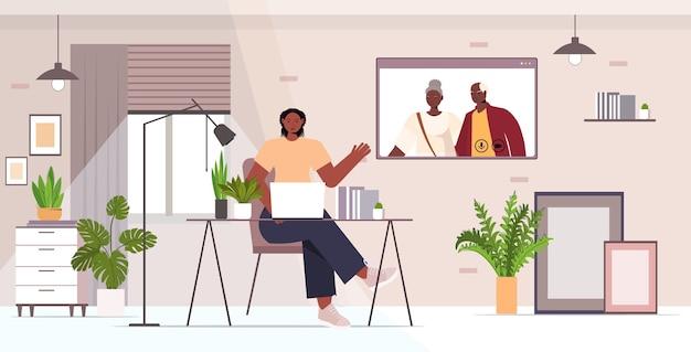 Geschäftsfrau, die virtuelles treffen mit älteren eltern während des videoanrufs familienchat online-kommunikationskonzept büro innenraum horizontal hat