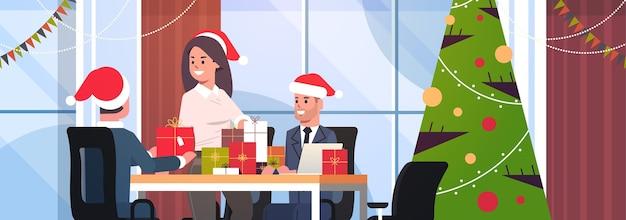 Geschäftsfrau gratuliert männlichen kollegen mit frohen weihnachten frohe neujahrsferien geschäftsleute am arbeitsplatz, die geschenkgeschenkboxen moderne büroinnenwohnung halten