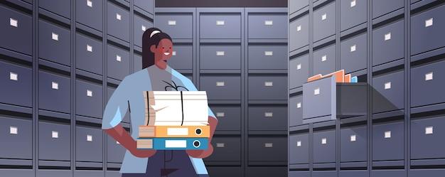 Geschäftsfrau hält pappkarton mit dokumenten im aktenwandschrank mit offener schublade datenarchivspeicher geschäftsverwaltungskonzept horizontale porträtvektorillustration